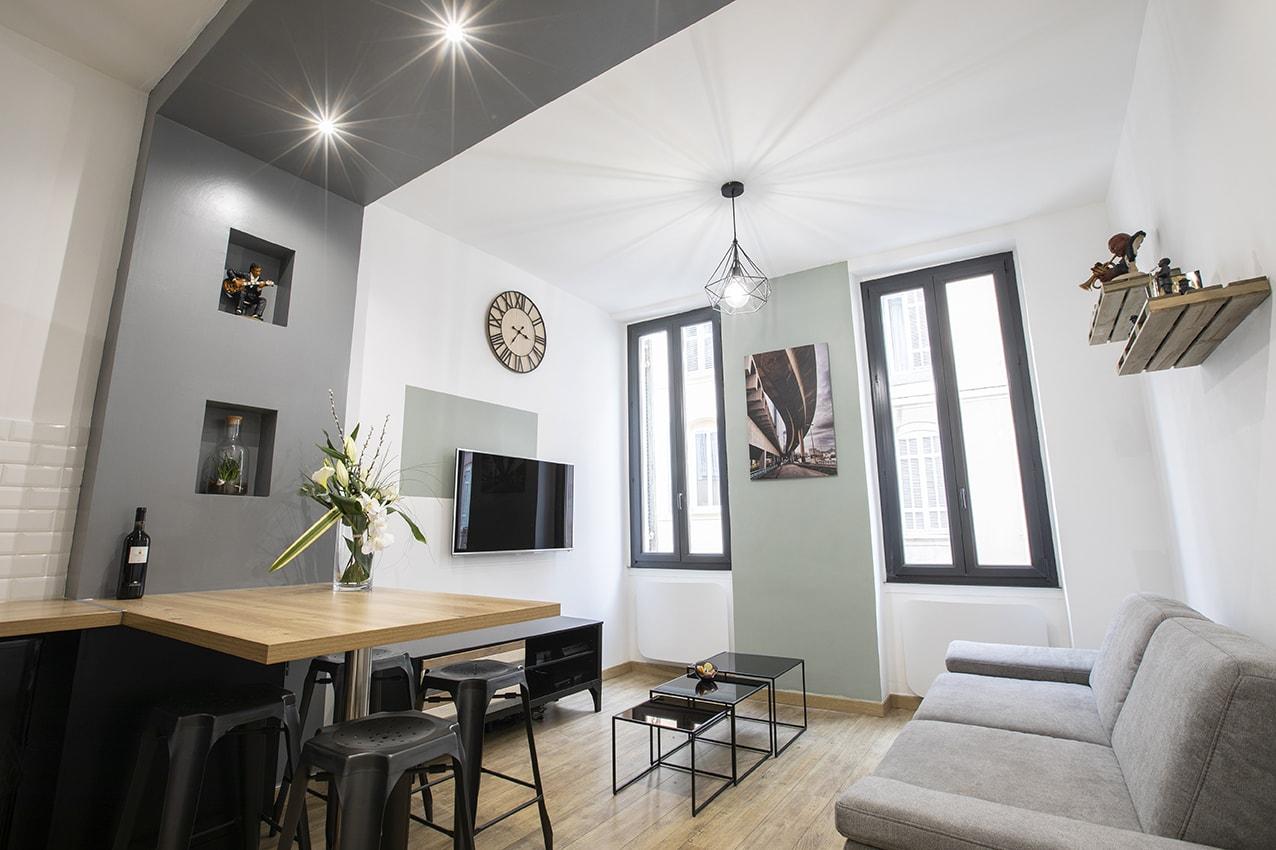 Les éléments vert de gris et noirs apportent modernité et soulignent les éléments architecturaux du studio.
