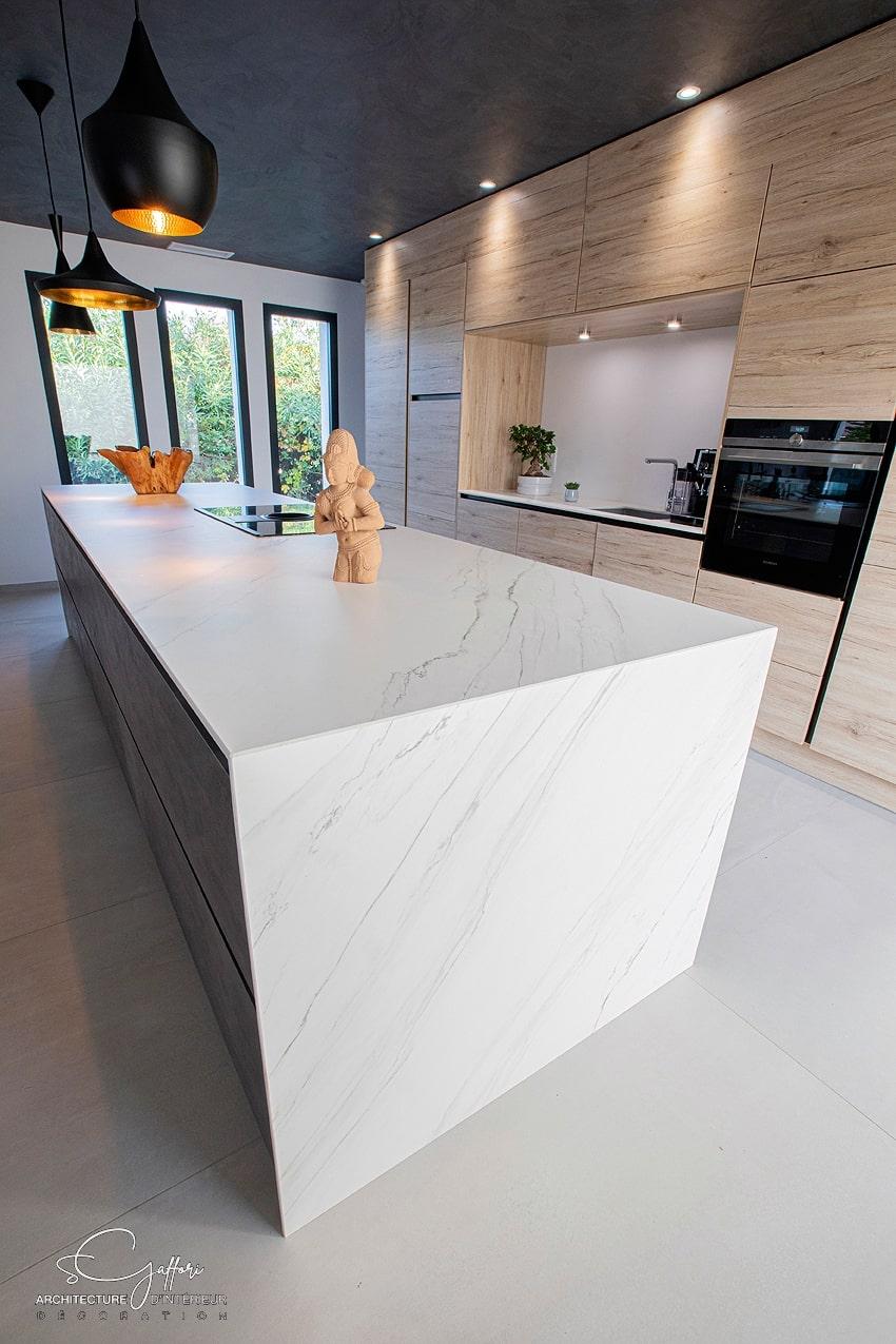 Le marbre recouvre les jambages de l'îlot profitant ainsi de ses qualités de robustesse. Il contraste avec le bois du meuble toute hauteur de fond, optimal en terme de rangement.