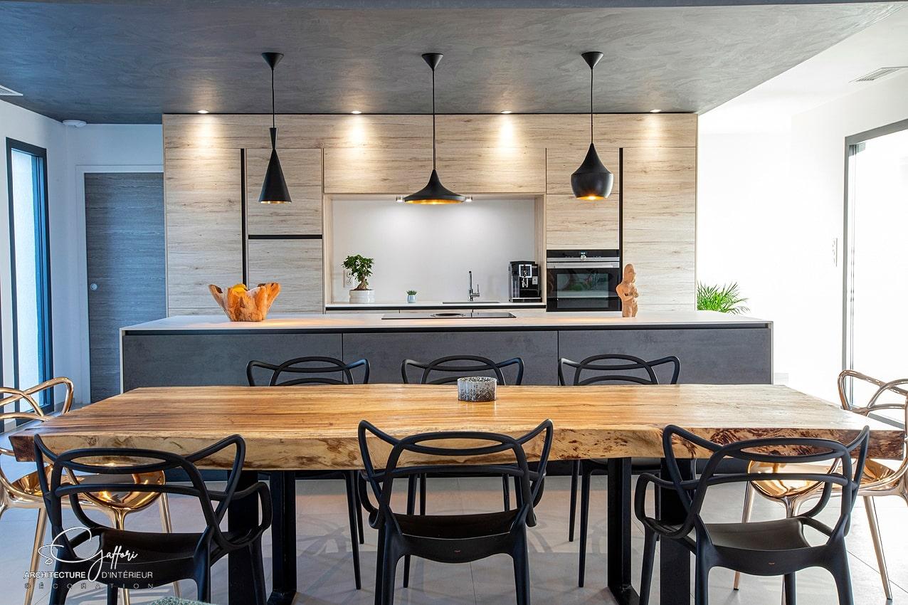 La cuisine est la pièce maîtresse du séjour. Elle est soulignée par un faux-plafond recouvert d'une peinture effet béton qui contraste avec la chaleur du bois.