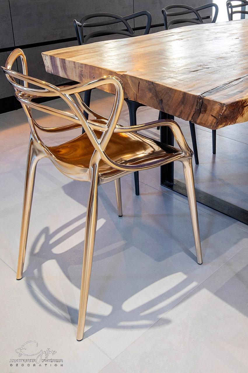 Les chaises très modernes contrastent avec le bois brut de la table créée sur mesure. 2 chaises de couleur or rose réhaussent celles de couleur noir mate.